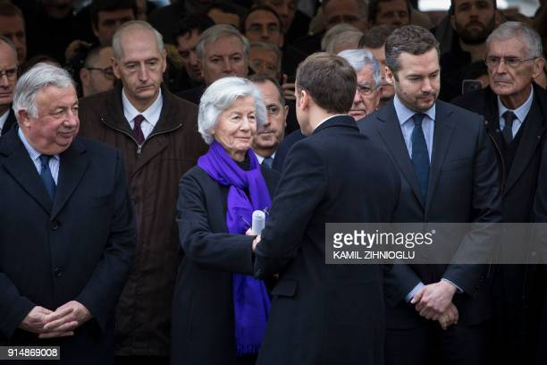 French President Emmanuel Macron shakes hand with Claude Erignac's widow Dominique Erignac flanked by French Senate President Gerard Larcher during...