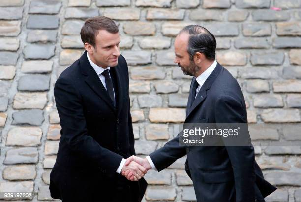 French President Emmanuel Macron shakes hand with French Prime minister Edouard Philippe prior to a solemn funeral ceremony for the Gendarme Colonel...