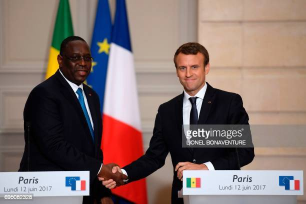 French President Emmanuel Macron shakes hand with his Senegalese counterpart Macky Sall after holding a joint press conference following their...