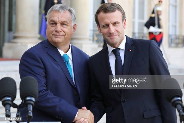 French President Emmanuel Macron shakes hand with Hungary's Prime minister Viktor Orban at the Elysee presidential palace before a meeting on October...