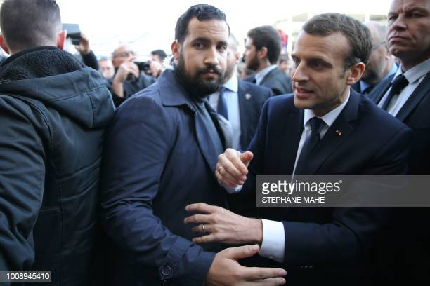 French President Emmanuel Macron shakes hands as Elysee senior security officer Alexandre Benalla looks on during a visit to the 55th International...