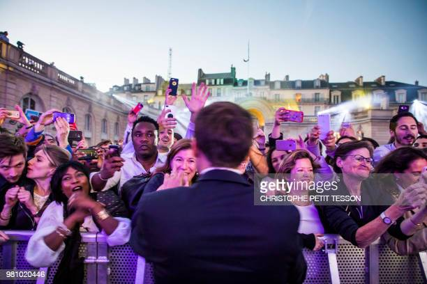 French president Emmanuel Macron shakes hands during the 'Fete de la Musique' the music day celebration in the courtyard of the Elysee Palace in...