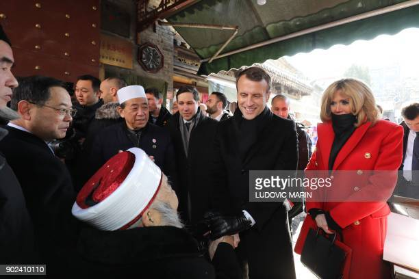 French President Emmanuel Macron shakes hands with a local elderly iman as his wife Brigitte Macron looks on during a visit to the Great Mosque of...