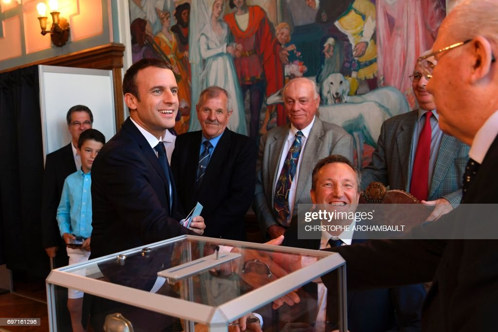French President Emmanuel Macron (L) shakes hands with a voting official after voting at a polling station in Le Touquet, northern France, during the second round of the French parliamentary elections (elections legislatives in French), on June 18, 2017. /