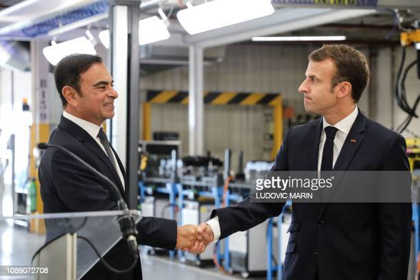 TOPSHOT French President Emmanuel Macron shakes hands with Chairman and CEO of RenaultNissanMitsubishi Carlos Ghosn during a visit of the Renault...