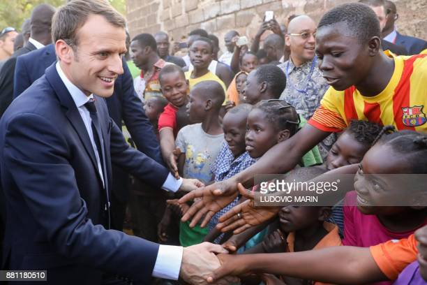 French President Emmanuel Macron shakes hands with children after visiting the Lagm Taaba school on November 28 in Ouagadougou as part of his first...