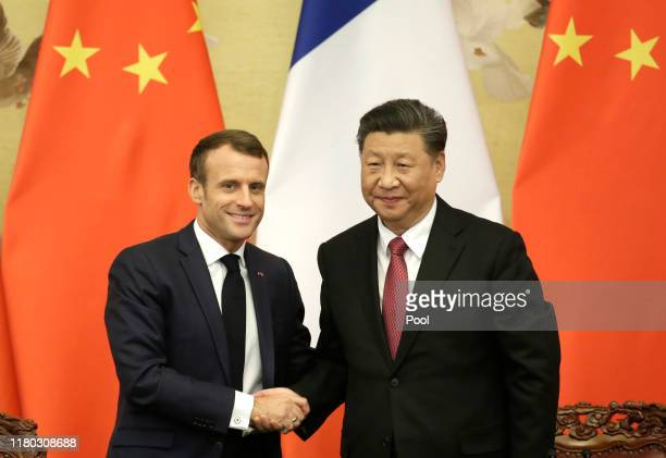 French President Emmanuel Macron shakes hands with China's President Xi Jinping after a joint news conference at the Great Hall of the People on...