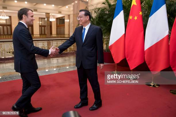 French President Emmanuel Macron shakes hands with Chinese Premier Li Keqiang as he arrives for a meeting at the Great Hall of the People in Beijing...