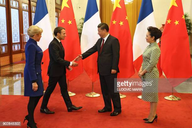 French President Emmanuel Macron shakes hands with Chinese President Xi Jinping as Brigitte Macron and Xi's wife Peng Liyuan look on during their...