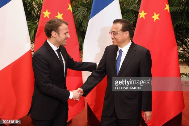 French President Emmanuel Macron shakes hands with Chinese Prime Minister Li Keqiang during their meeting in Beijing on January 9 2018 Macron is on...