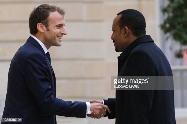French president Emmanuel Macron shakes hands with Ethiopian Prime Minister Abiy Ahmed as he welcomes him upon his arrival at the Elysee Palace ahead...