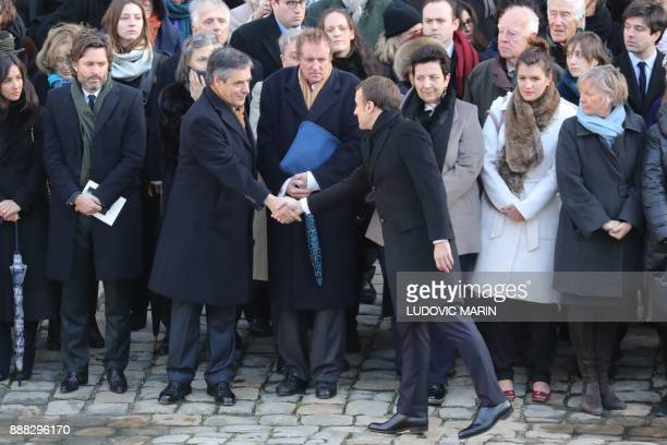 French President Emmanuel Macron shakes hands with former French Prime Minister Francois Fillon during the National Tribute ceremony for late member...