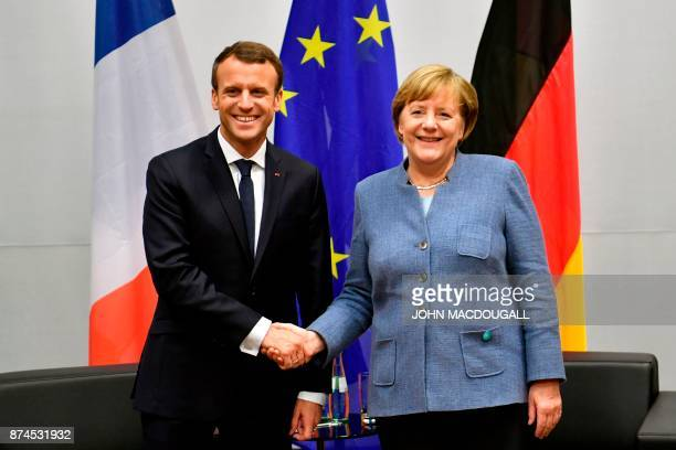 French President Emmanuel Macron shakes hands with German Chancellor Angela Merkel during bilateral talks on the sidelines of the UN conference on...