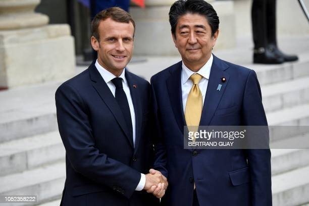 TOPSHOT French President Emmanuel Macron shakes hands with Japanese Prime Minister Shinzo Abe after a meeting at the Elysee Palace in Paris on...