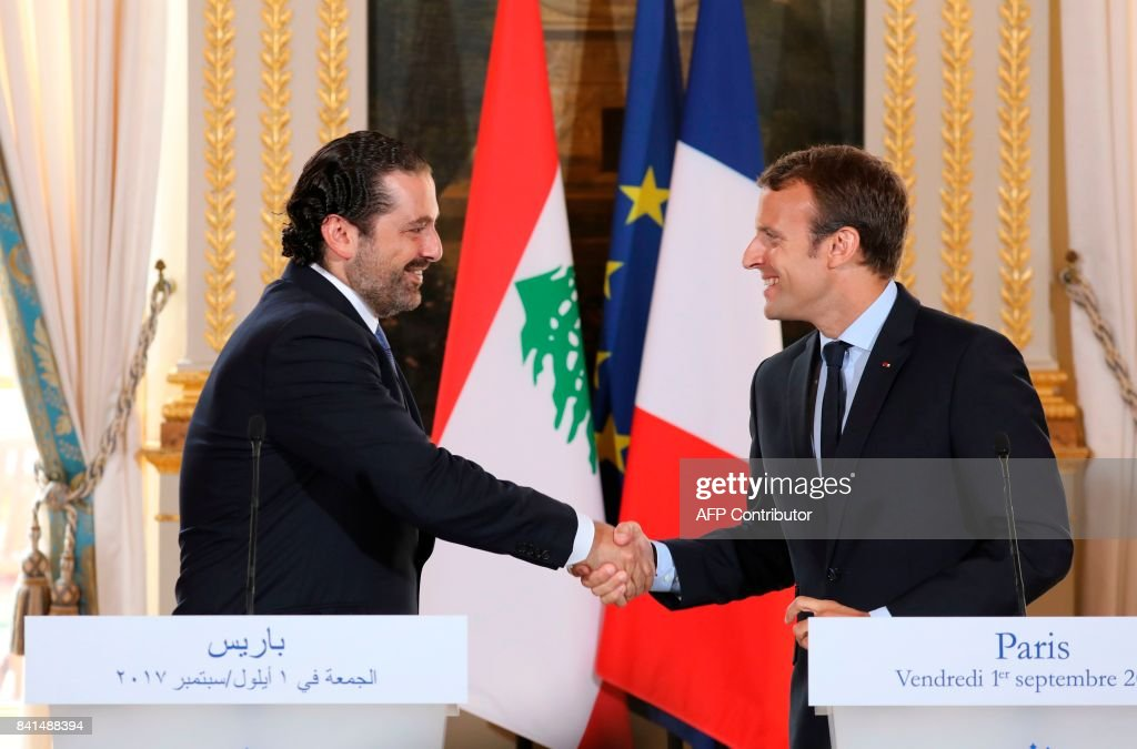 French President Emmanuel Macron (R) shakes hands with Lebanese Prime Minister Saad Hariri during a press conference at the Murat Lounge in the Elysee Palace in Paris on September 1, 2017. / AFP PHOTO / ludovic MARIN