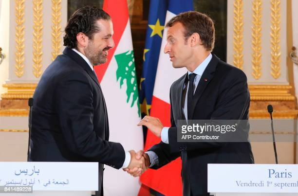 French President Emmanuel Macron shakes hands with Lebanese Prime Minister Saad Hariri during a press conference at the Murat Lounge in the Elysee...