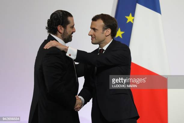 TOPSHOT French President Emmanuel Macron shakes hands with Lebanese Prime Minister Saad Hariri during the International CEDRE Conference on April 6...
