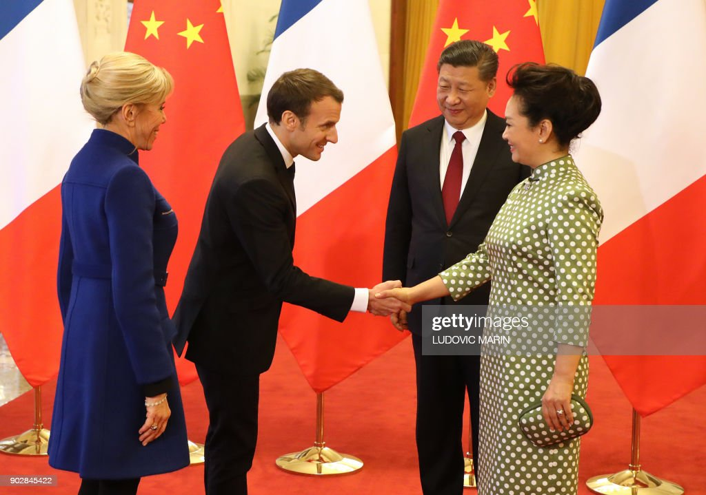 French President Emmanuel Macron (2nd L) shakes hands with Peng Liyuan (R), wife of Chinese President Xi Jinping (2nd R), as Brigitte Macron (L) looks on, during their meeting at the Great Hall of the People in Beijing on January 9, 2018. Macron is on the second day of his visit to the Chinese capital. / AFP PHOTO / POOL / ludovic MARIN