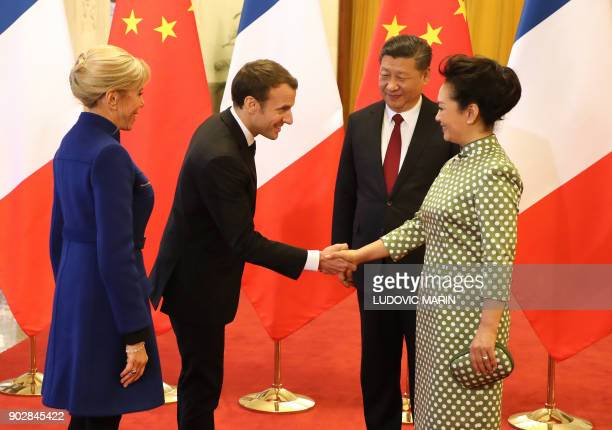 French President Emmanuel Macron shakes hands with Peng Liyuan wife of Chinese President Xi Jinping as Brigitte Macron looks on during their meeting...