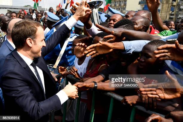 French President Emmanuel Macron shakes hands with people as he is greeted by crowds at the Treichville Train Station in Abidjan on November 30 after...