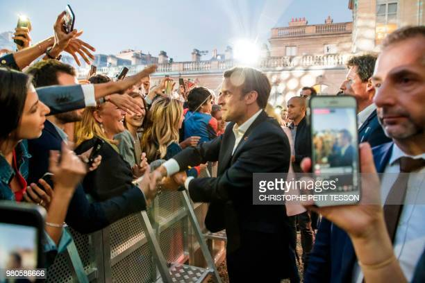French president Emmanuel Macron shakes hands with people during the annual Fete de la Musique in the courtyard of the Elysee Palace in Paris on June...