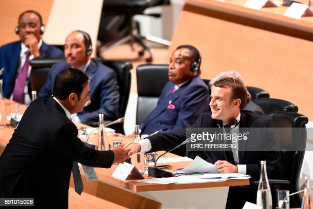 French President Emmanuel Macron shakes hands with RenaultNissan Chairman and CEO Carlos Ghosn during the One Planet Summit on December 12 at La...