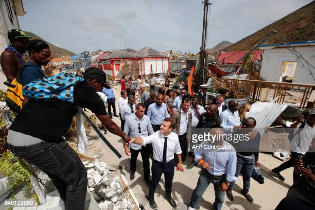 French President Emmanuel Macron shakes hands with residents during a visit to the French Caribbean island of St Martin on September 12 2017 French...