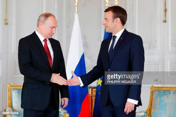 French President Emmanuel Macron shakes hands with Russian President Vladimir Putin at the Chateau de Versailles as they meet for talks in Versailles...