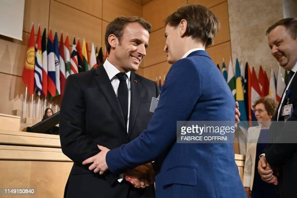 French President Emmanuel Macron shakes hands with Serbian Prime Minister Ana Brnabic prior to deliver a speech at the International Labour...