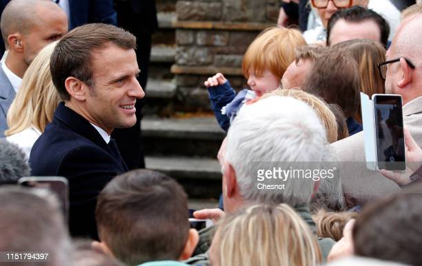 French President Emmanuel Macron shakes hands with supporters as he leaves the polling station after casting his vote in the European elections on...