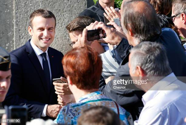 French President Emmanuel Macron shakes hands with supporters as he leaves the polling station of the the town hall after casting his vote in the...