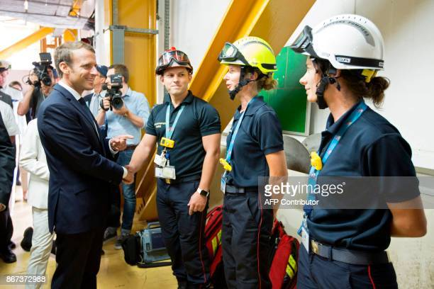 French President Emmanuel Macron shakes hands with technicians during a visit to the Guiana Space Centre in Kourou on October 27 2017 as part of a...