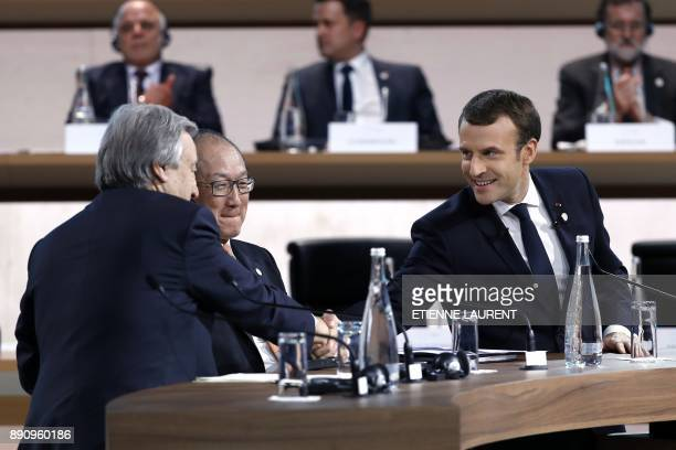 French President Emmanuel Macron shakes hands with United Nations Secretary General Antonio Guterres during the One Planet Summit on December 12 at...