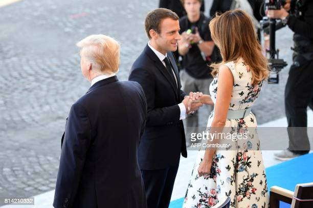 French President Emmanuel Macron shakes hands with US First Lady Melania Trump next to US President Donald Trump during the annual Bastille Day...