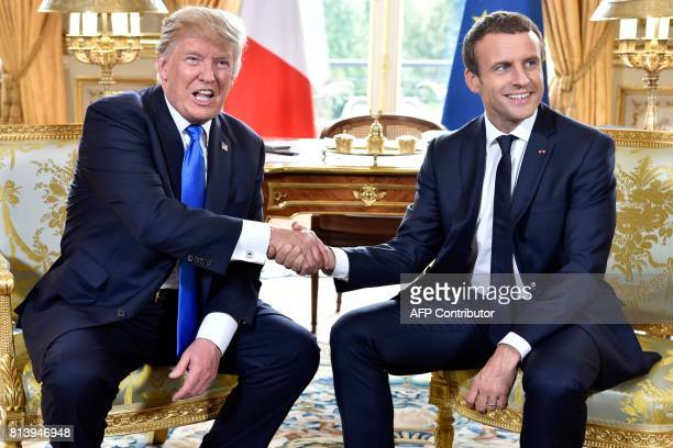 French President Emmanuel Macron shakes hands with US President Donald Trump during their meeting at the Elysee Palace in Paris on July 13 during...