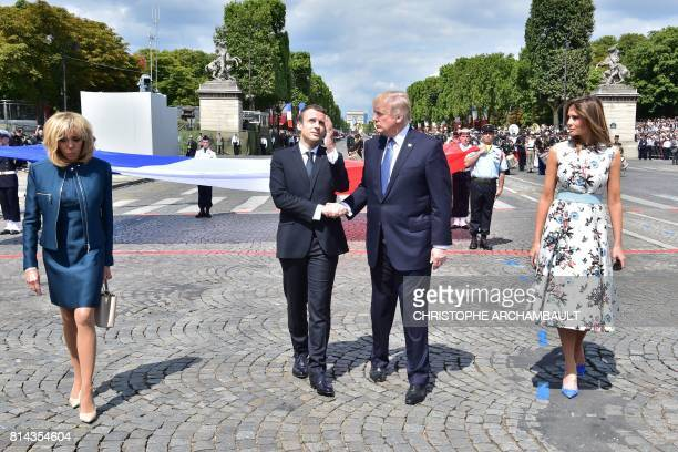 French President Emmanuel Macron shakes hands with US President Donald Trump next to Macron's wife Brigitte Macron and US First Lady Melania Trump...