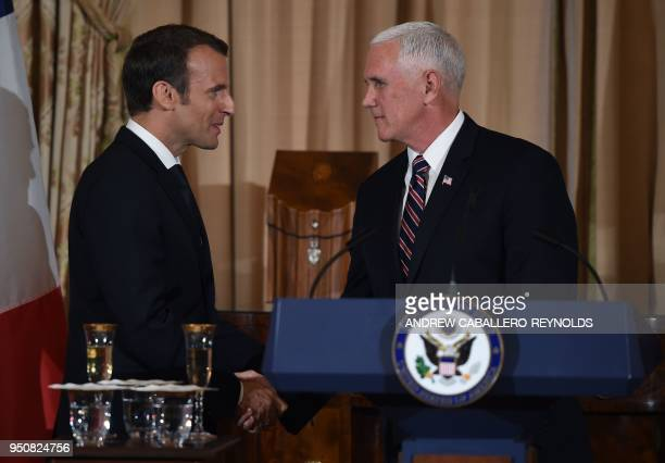 French President Emmanuel Macron shakes hands with US Vice President Mike Pence during a luncheon at the US State Department in Washington DC on...