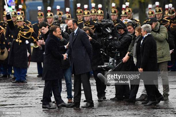 French President Emmanuel Macron shakes the hand of French Prime Minister Edouard Philippe as he arrives for the 11th November commemoration at the...