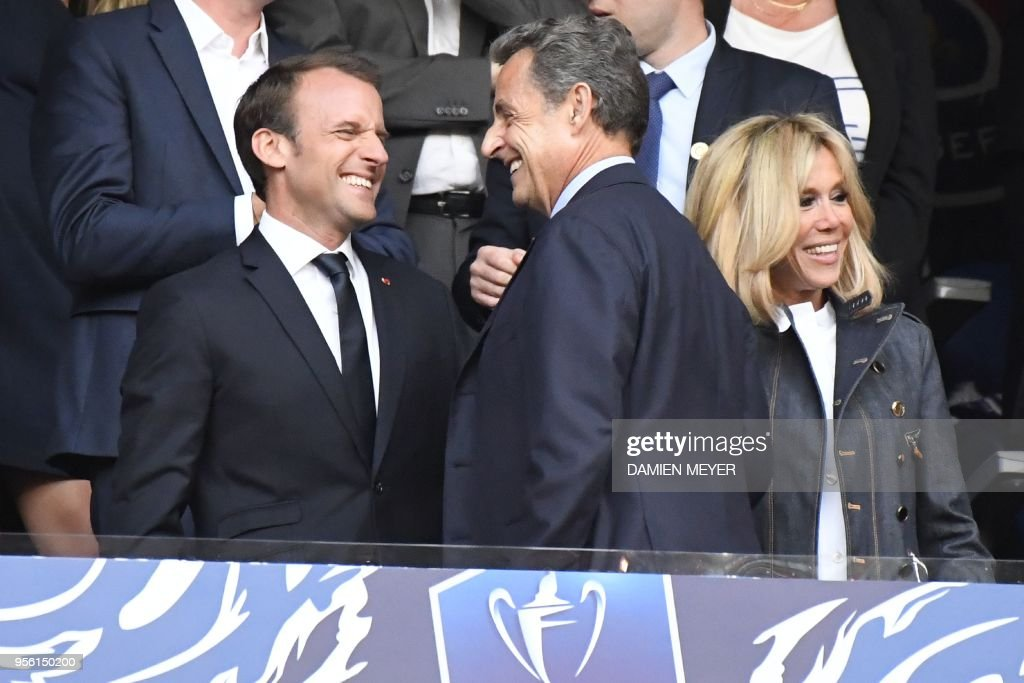 TOPSHOT - French president Emmanuel Macron (L) shares a laugh with former French president Nicolas Sarkozy (C) next to his wife ahead of the French Cup final football match between Les Herbiers and Paris Saint-Germain (PSG), on May 8, 2018 at the Stade de France in Saint-Denis, outside Paris.