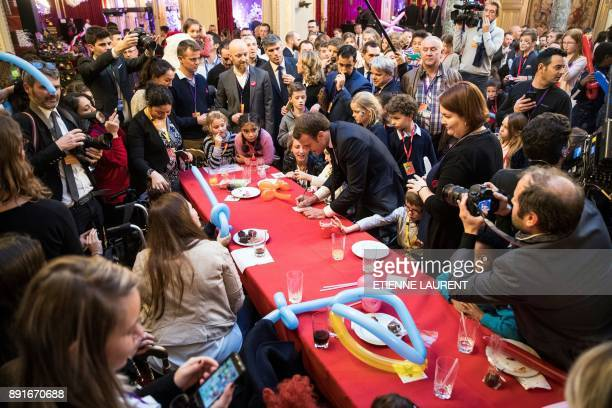 French President Emmanuel Macron signs an autograph on December 13 at the Elysee Presidential palace in Paris as he attends the Elysee Christmas...