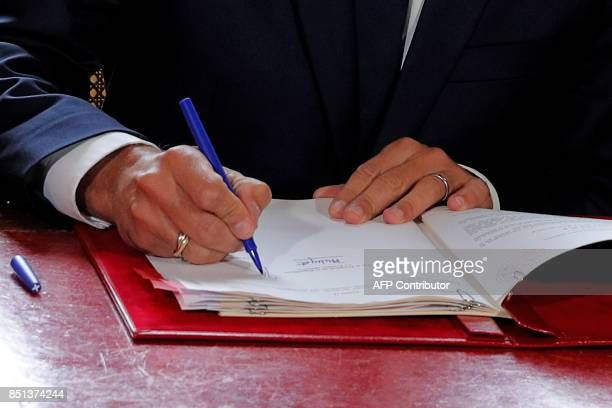 French President Emmanuel Macron signs documents in front of the media to promulgate a new labour bill in his office at the Elysee Palace in Paris on...