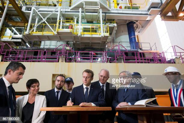 French President Emmanuel Macron signs the guest book as French Minister of Public Action and Accounts Gerald Darmanin French Overseas Minister...