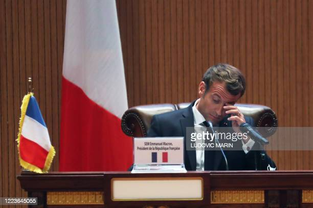 French President Emmanuel Macron sits at a desk during the closing press conference at the G5 Sahel summit on June 30 in Nouakchott. - The leaders of...
