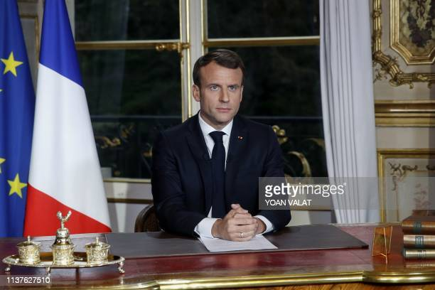 French President Emmanuel Macron sits at his desk after addressing the nation on April 16 2019 during which he vows to rebuild NotreDame de Paris...