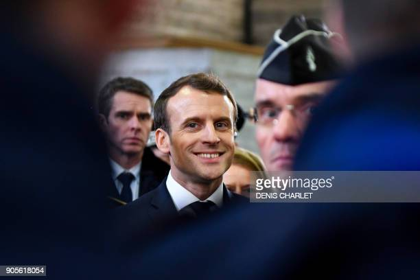 French President Emmanuel Macron smiles as he meets gendarmerie and police forces during his visit in the French northern city of Calais on January...