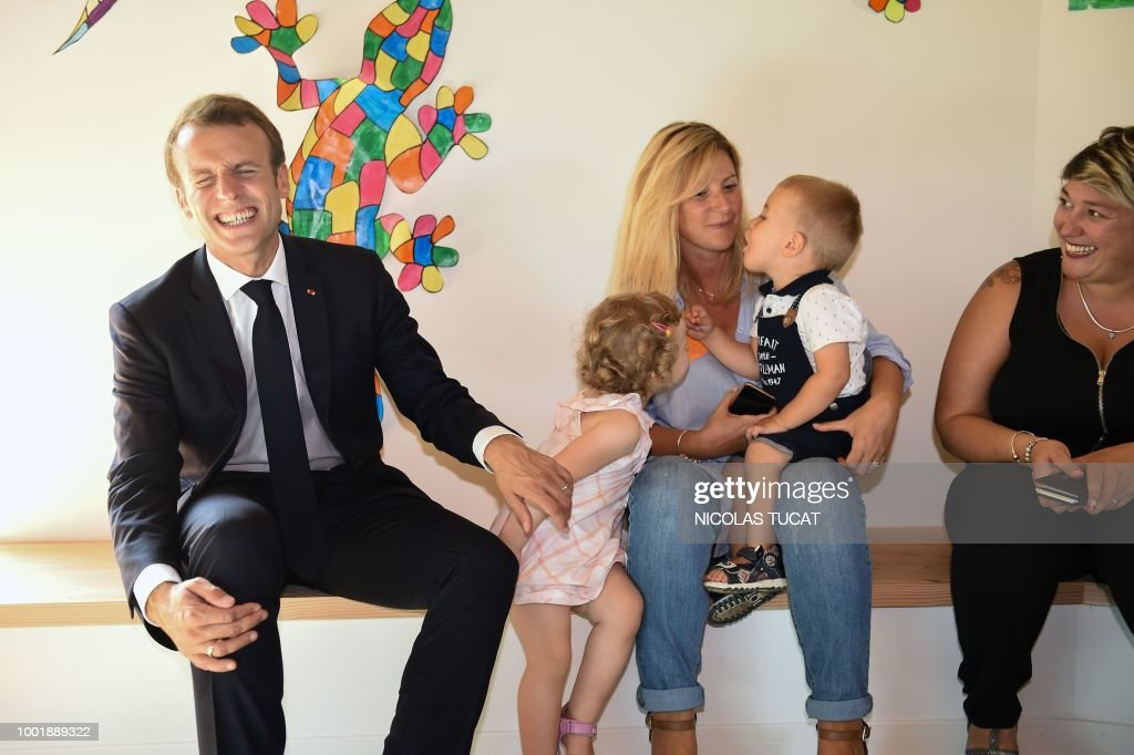 French President Emmanuel Macron (L) smiles during his visit to a nursery school at the new public services building following its inauguration in Sarliac-sur-l'Isle, southwestern France, during a visit to the Dordogne region, on July 19, 2018.
