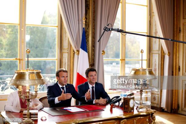 French President Emmanuel Macron speaks flanked by French Government's spokesperson Benjamin Griveaux during an event to sign documents enacting a...