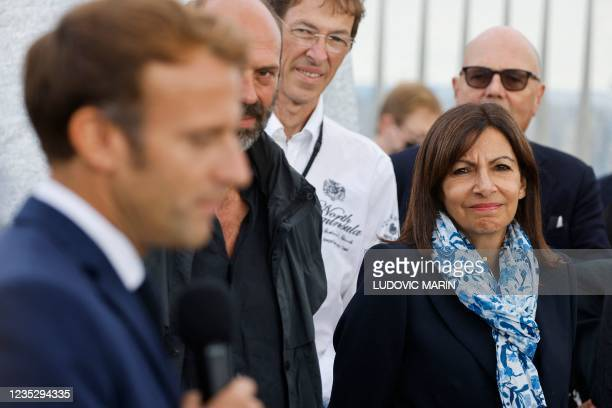 French President Emmanuel Macron speaks near Paris Mayor and Socialist Party candidate for the 2022 French presidential elections Anne Hidalgo during...