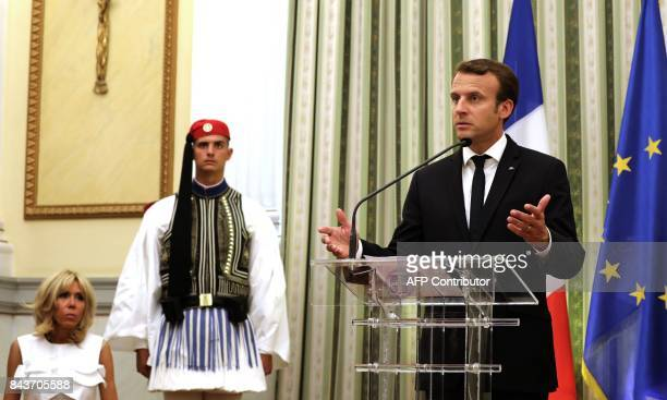 French president Emmanuel Macron speaks next to his wife Brigitte Macron and a Greek guard during a welcoming ceremony at the presidential palace in...