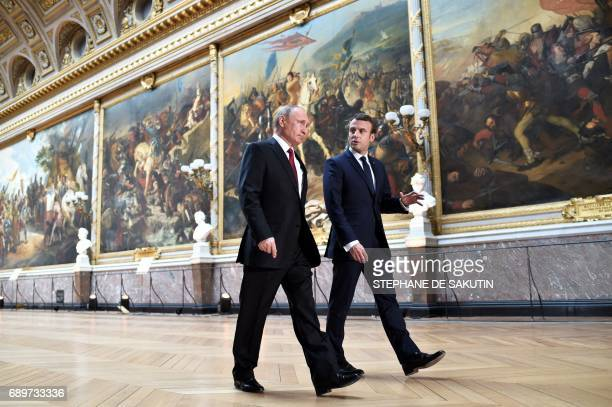 TOPSHOT French President Emmanuel Macron speaks to Russian President Vladimir Putin in the Galerie des Batailles as they arrive for a joint press...